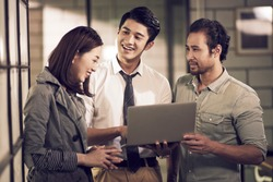 a team of three young asian businesspeople entrepreneurs having a discussion using laptop computer in office happy and smiling