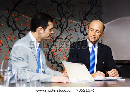 A Team Of Two Executive Business People Plan And Develop Future Business Growth While Looking Through Files And Documents During A Boardroom Meeting