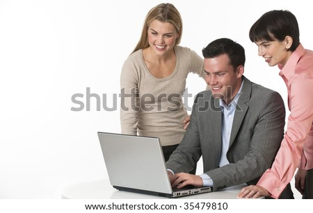 A team of two females and one male working together at a computer. They are smiling. Horizontally framed shot.