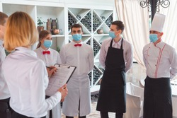 a team of waiters conduct a briefing on the summer terrace of the restaurant.
