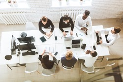 A team of young businessmen sitting at the table, top view, working and communicating together in an office. Corporate businessteam and manager in a meeting.