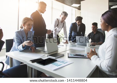 A team of young businessmen working and communicating together in an office. Corporate businessteam and manager in a meeting. #1411448804