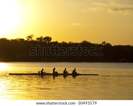 A team of young mean in a row boat silhouetted against setting sun