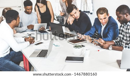 A team of young office workers, businessmen with laptop working at the table, communicating together in an office. Corporate businessteam and manager in a meeting. coworking. #1467880160
