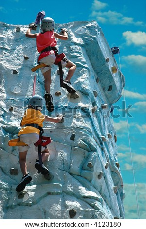 A team (two kids) climbing the top of a rock wall
