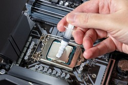 A technician applies white thermal paste to the CPU. Installing a cooler on a PC processor. Assembling or upgrading a Personal Computer