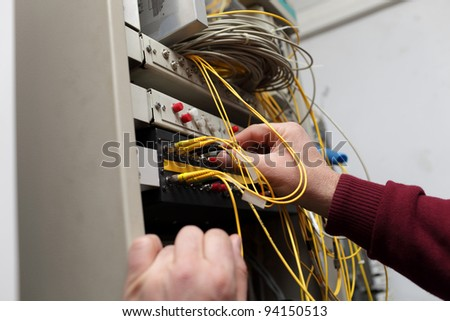 A technician attaching optical connector to ODF at a server room