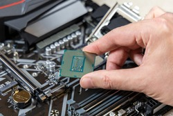 A technician holds the CPU Intel against the background of the motherboard Gigabyte. Computer parts. PC assembly concept