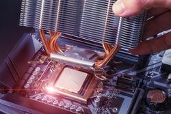 A technician installs an aluminum air-cooled heatsink on a desktop PC CPU. Air Cooler CPU. PC assembly and modernization