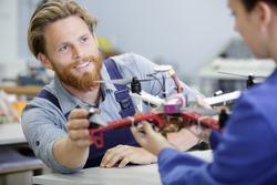 a technician is repairing quadrocopter drone