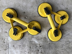 A technician's tool with glass expertise called a glass sucker to lift. 3 legs glass sucker painted in yellow. A top-down look of two yellow glass suckers placed on an old foam floor.