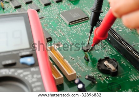 A technician testing a motherboard using multimeter