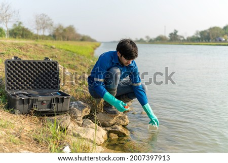 A technician use the Professional Water Testing equipment to measure the water quality at the public canal. Portable multi parameter water quality measurement. Water quality monitoring concept.