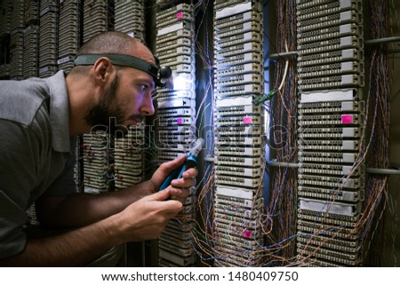 A technician with a flashlight on his head works in a dark server room. The specialist fixes the problem of communication. Man cuts a telephone wire near a patch cross panel.