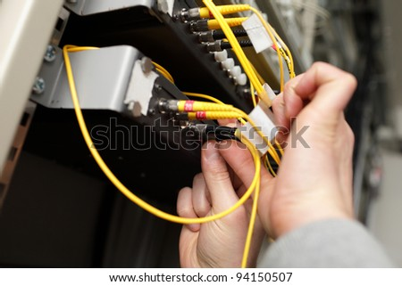 A technician with optical connector at telecom site