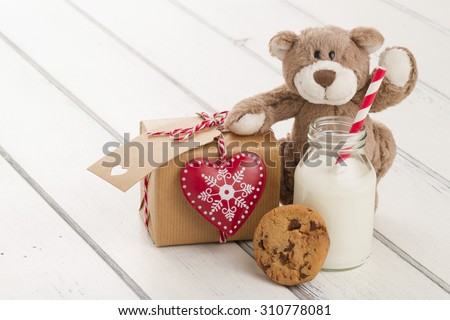 A teddy bear, a red heart and a school milk bottle with a straw on a white wooden table. A paper parcel (christmas gift box) wrapped with paper kraft and tied with red & white baker\'s twine.