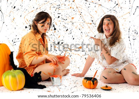 A teen and preteen making a Halloween mess with black and orange pain.  A black cat and pumpkins nearby.