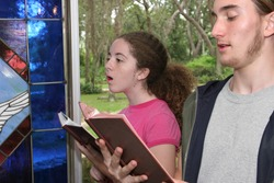 a teen boy and girl  singing hymns in church (focus is on girl)