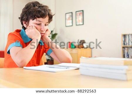 A teen boy learning over his homework reading his workbook.