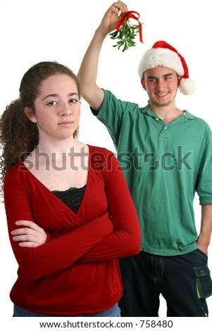 stock photo : A teen girl avoiding a teen boy who has mistletoe. Focus on