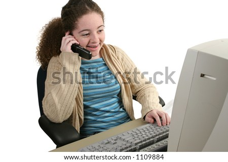 A teen girl doing her homework online and chatting on her cell phone.  Isolated.