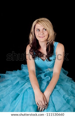 A teen girl in her baby blue ruffled dress with her hands in her laps and a smile on her face.