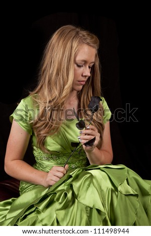 a teen girl in her beautiful green formal looking down at a black rose.