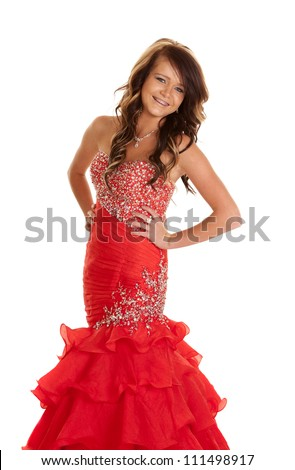 A teen girl in her formal dress posing with a smile on her face.