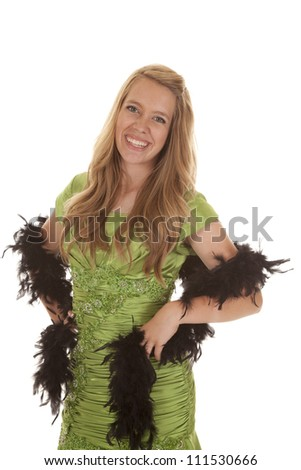 A teen girl in her green formal with her black feathered boa on her arms.
