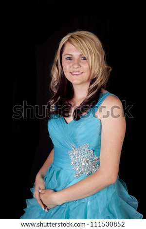 A teen girl in her prom dress with a smile on her face.