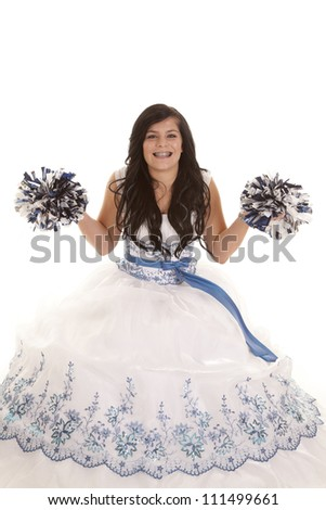 a teen girl in her white formal dress with a smile on her face holding up her pom poms