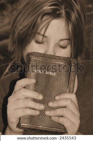 a teen girl praying while holding the bible