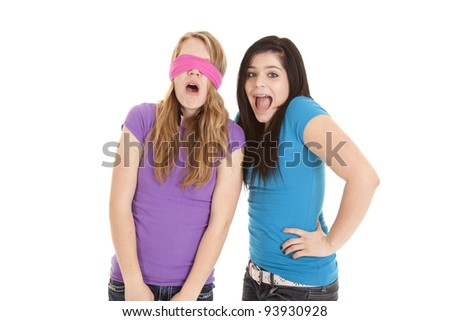 A teen girl putting a pink blindfold over her friends eyes.