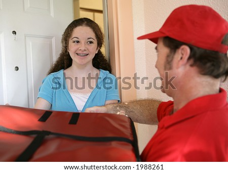 A teen girl receiving a pizza delivered to her home.