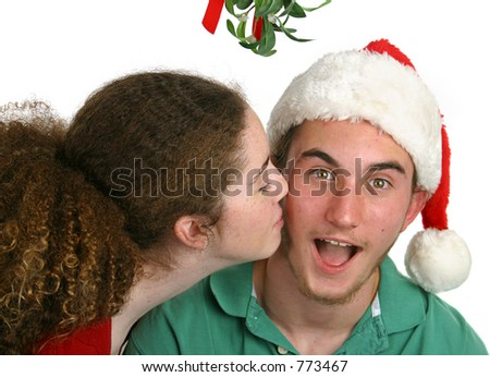 A teen girl surprising a teen boy with a kiss under the mistletoe.  Isolated.