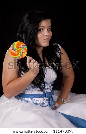 a teen girl with a funny expression on her face in her formal dress holding on to a colorful sucker