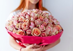 a teen girl with a huge bouquet of roses in her hands