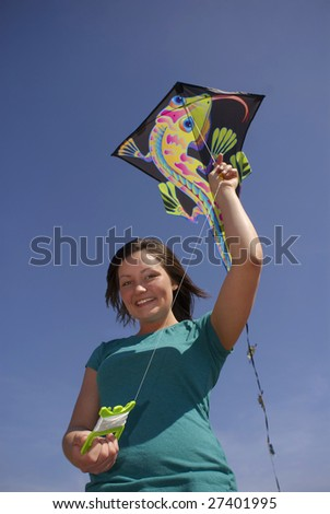 A teen smiles while holding a colorful kite on a windy spring day.