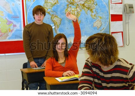 A Teen student raises hand in classroom