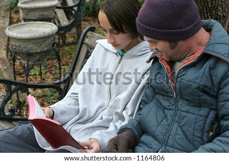 A teen volunteer reading the bible to a homeless person. Focus on the teen\'s face