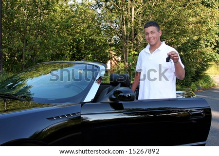 A teenage boy holding the keys to an expensive convertible hoping to drive.