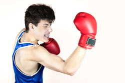 A teenage boy in blue boxing uniform and red gloves punches an uppercut from below on a light background. The guy has an angry face, he is really good but he has an sports anger in battle