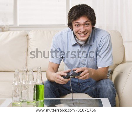 A teenage boy is sitting on his couch and playing video games.  He is smiling at the camera.  Horizontally framed shot.