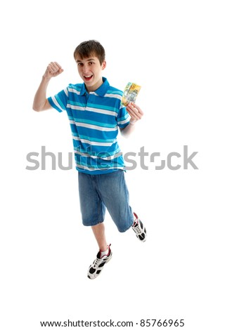 A teenage boy leaps for joy and makes a fist of success.  He is holding some money in the other hand.  White background.