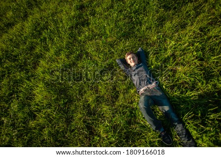 A teenage boy lies on the green grass lawn smiling and resting. View from above. Copy space. Сток-фото ©