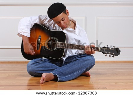 A teenage boy practicing his guitar.