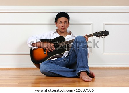 A teenage boy, sitting on the floor with his guitar.