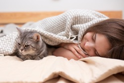 A teenage girl and a tabby cat lying under a blanket on the bed and sleep. Keeping warm in the cold winter Pets and friendship concept. Quarantine. Holidays. Stay home. Self-isolation. Social distance