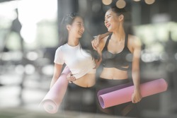 A teenage girl friend is walking holding a purple yoga mats after giving up yoga at gym, A photo through a glass window of a young Asian woman talking and laughing at a fitness facility.