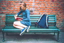A teenage girl is reading on a bench with brick wall in the background. Toned image